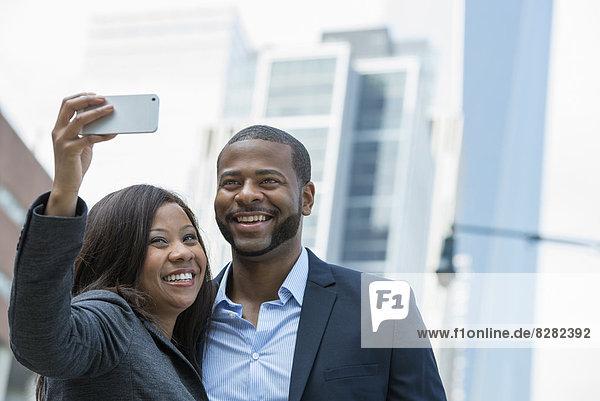 Sommer. Ein Paar  das sich selbst fotografiert  eine Frau  die ein Smartphone in der Hand hält und ein Foto von sich macht.
