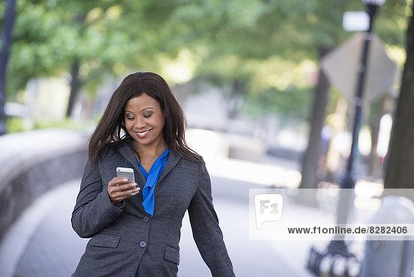 Sommer. Eine Frau in einem grauen Anzug mit einem hellblauen Hemd. Mit einem Smartphone.