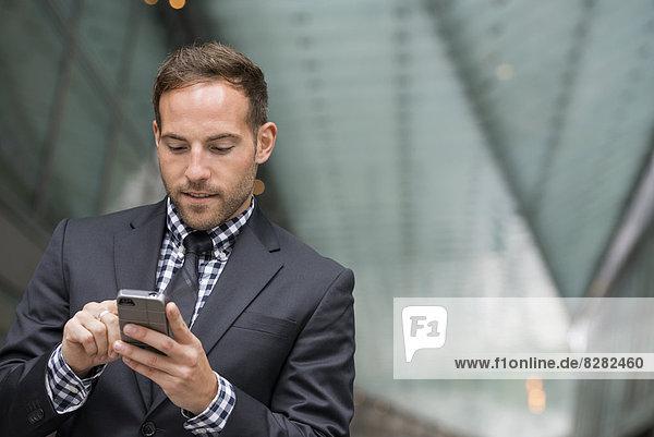 Geschäftsleute. Ein Mann in einem Geschäftsanzug. Ein Mann mit kurzen roten Haaren und einem Bart in einem Anzug am Telefon.