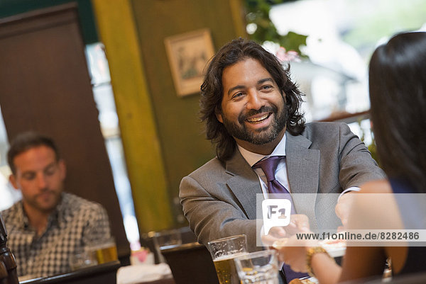 Geschäftsleute. Zwei Personen  die an einem Tisch sitzen und sich an den Händen halten. Ein Mann im Hintergrund.