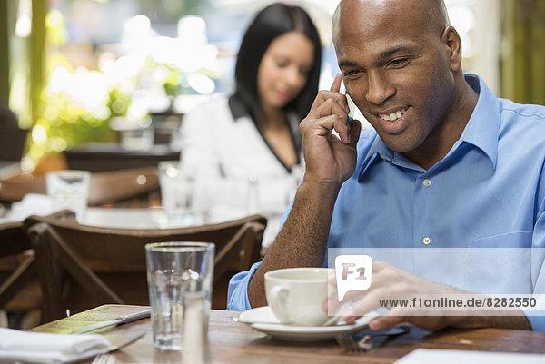 sitzend  Mensch  zwei Personen  Menschen  Wirtschaftsperson  2  Laden  Kaffee