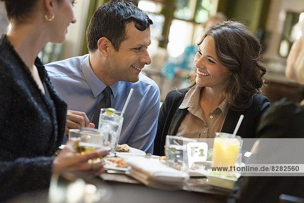 Geschäftsleute. Vier Personen  ein Mann und drei Frauen sitzen an einem Tisch.