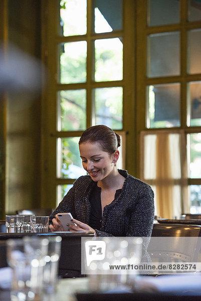 Geschäftsleute. Eine Frau  die allein an einem Tisch sitzt. Kontrolle ihres Telefons.