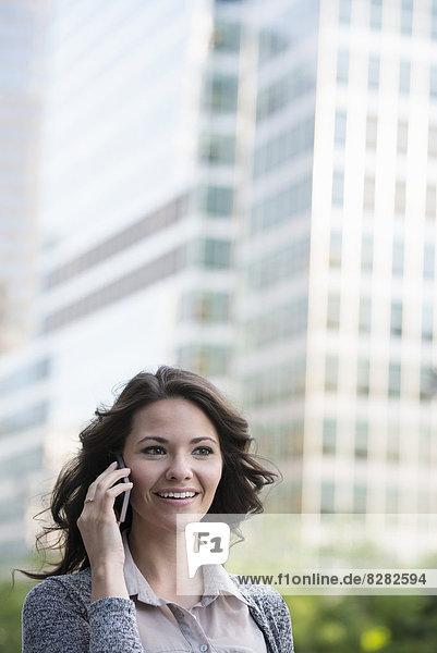 Geschäftsleute. Eine Geschäftsfrau in hellgrauer Jacke  die ihr Smartphone benutzt.