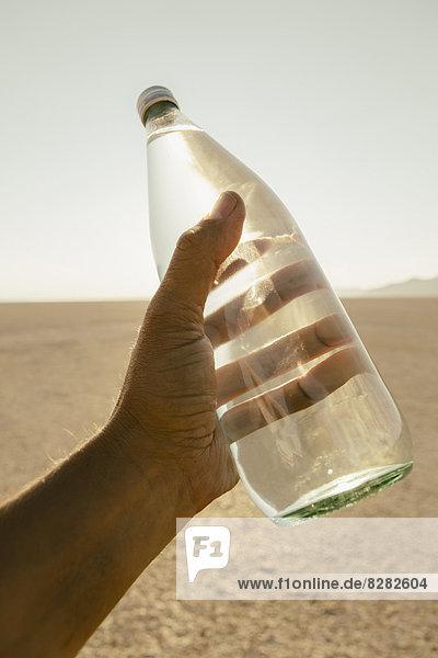 Die Landschaft der Schwarzen Felsenwüste in Nevada. Eine Männerhand hält eine Flasche Wasser. Gefiltertes Mineralwasser.