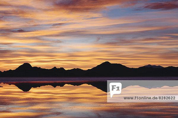 Der Himmel bei Sonnenuntergang. Wolkenschichten  die sich im seichten Wasser spiegeln  das die Bonneville Salt Flats überflutet