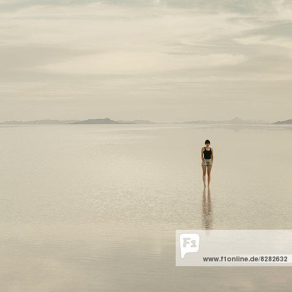 Frau  die in der Abenddämmerung auf den überfluteten Bonneville-Salinen steht.