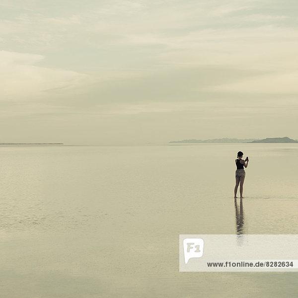 Eine Frau steht auf den überfluteten Salzseen von Bonneville und fotografiert mit einem Smartphone.
