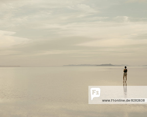 Eine Frau steht in der Abenddämmerung auf den überfluteten Bonneville-Salinen. Reflexionen im flachen Wasser.