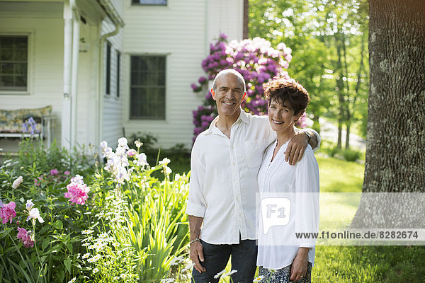 Organic Farm. Summer Party. A Mature Couple In White Shirts Standing Together Among The Flowers.