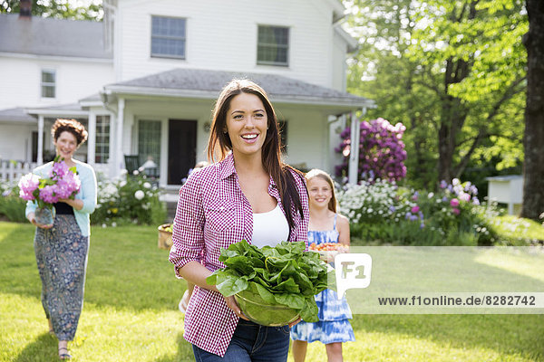 Family Party. Parents And Children Walking Across The Lawn Carrying Flowers  Fresh Picked Vegetables And Fruits. Preparing For A Party.