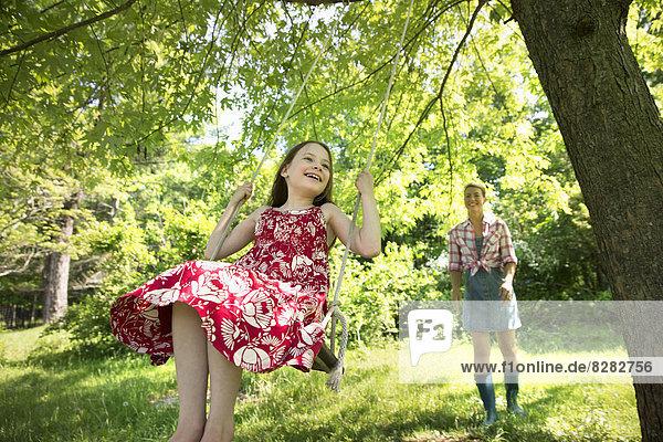 Sommer. Ein Mädchen in einem Sonnenkleid auf einer Schaukel unter einem blattreichen Baum. Eine Frau  die hinter ihr steht.