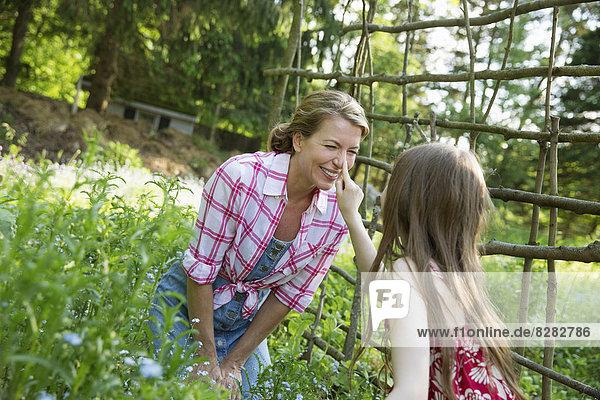 Eine Mutter und eine Tochter zusammen in einem Pflanzengehege in einem Garten. Grüne Blattpflanzen. Ein Kind berührt die Nase einer erwachsenen Frau.