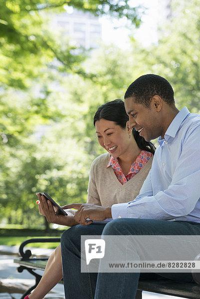 Sommer. Geschäftsleute. Ein Mann und eine Frau sitzen mit einem digitalen Tablet und bleiben in Kontakt.