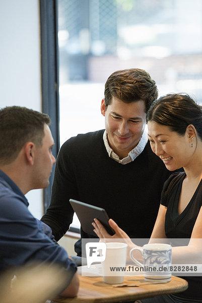 Eine Gruppe von Menschen,  die um einen Tisch in einem Kaffeehaus sitzen. Sie schauen auf den Bildschirm eines digitalen Tabletts.