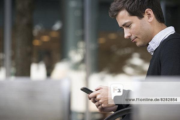Sommer in der Stadt. Ein Mann sitzt auf einer Bank und benutzt ein Smartphone.