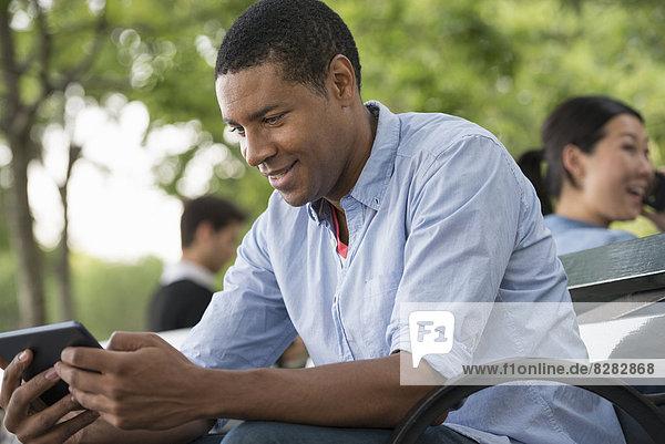 Sommer. Ein Mann sitzt auf einer Bank und benutzt ein digitales Tablett.