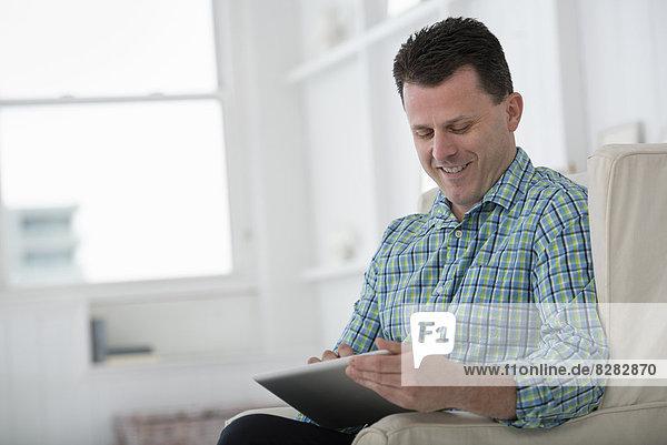 Ein Mann sitzt in einem Sessel und benutzt ein digitales Tablett.