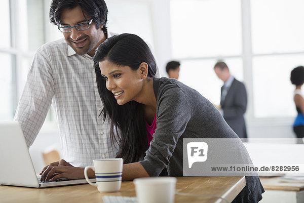 Büro. Ein Mann und eine Frau benutzen einen Laptop-Computer.