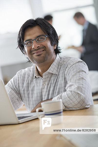 Ein junger Mann in einem Büro mit einem Laptop-Computer.
