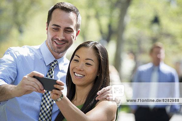 Ein Paar mit einem Smartphone  Seite an Seite. Ein Mann im Hintergrund.