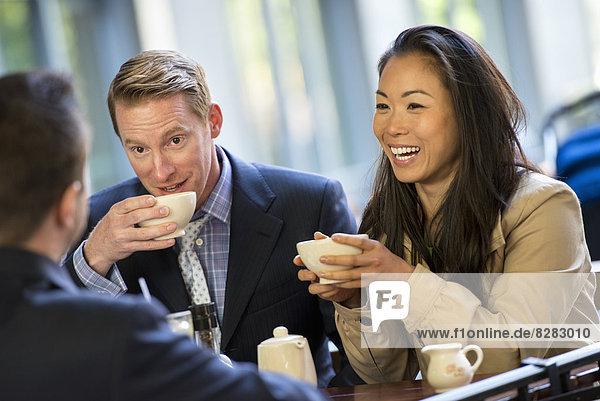 Eine Geschäftsfrau und zwei Geschäftsleute sitzen in einem Coffee Shop und trinken eine Tasse Kaffee.