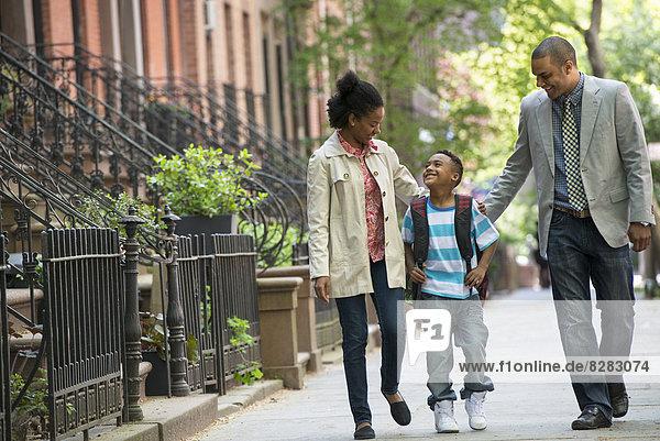 Eine Familie im Freien in der Stadt. Zwei Eltern und ein junger Junge gehen zusammen spazieren.