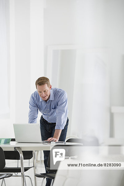 Business. A Man Standing Over A Desk  Leaning Down To Use A Laptop Computer.