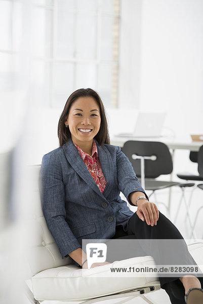 Wirtschaft. Eine Frau  die entspannt auf einem bequemen Stuhl sitzt.