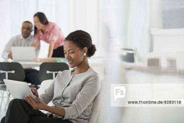Wirtschaft. Eine Frau  die sich mit einem digitalen Tablett hinsetzt. Zwei Personen im Hintergrund  die auf einen Computerbildschirm schauen.
