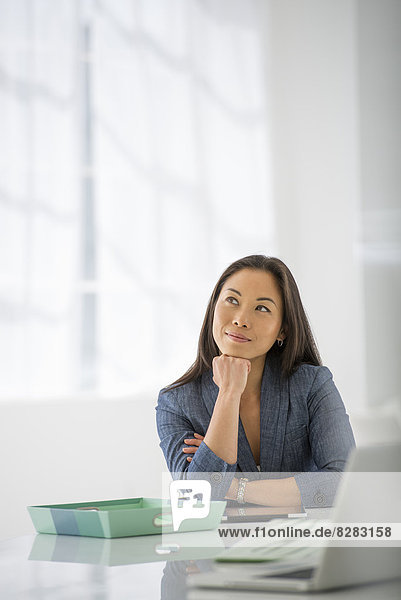 Business. A Woman Sitting Relaxing  With Her Chin On Her Hand.