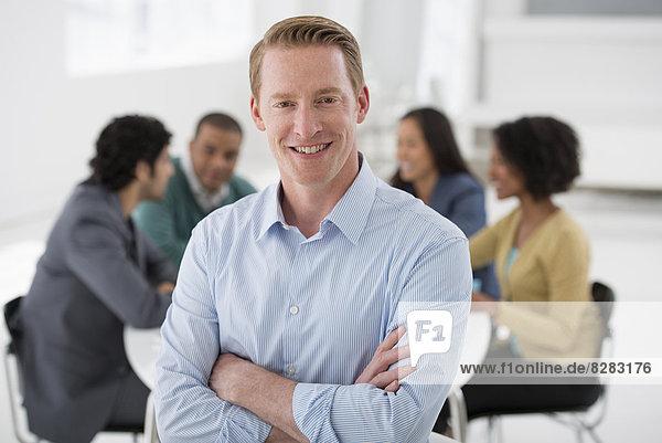 Geschäftstreffen. Eine Gruppe  die sich um einen Tisch versammelt. Ein Mann  der selbstbewusst lächelt.