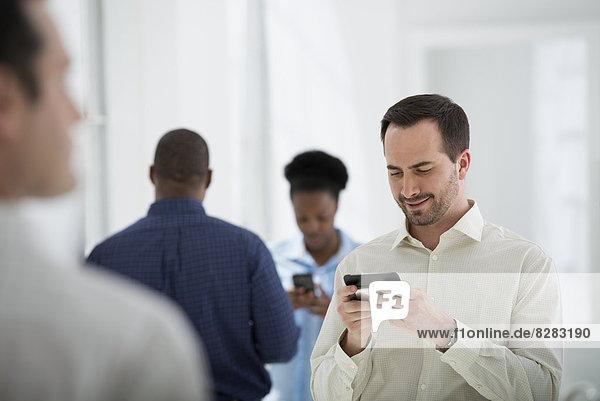 Innenministerium. Eine Gruppe von Menschen  ein Mann mit einem Smartphone.