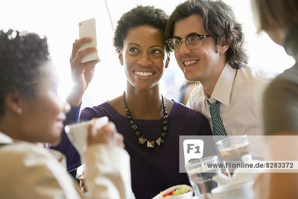 Stadtleben. Eine Gruppe von Menschen in einem CafÈ  die ihre Smartphones überprüfen.