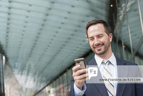 Stadt. Ein Mann im Geschäftsanzug  der seine Nachrichten auf seinem Smartphone abruft.