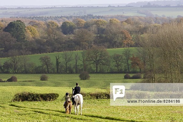 Mother and daughter ride together through rolling hills and fields in Oxfordshire  The Cotswolds  UK