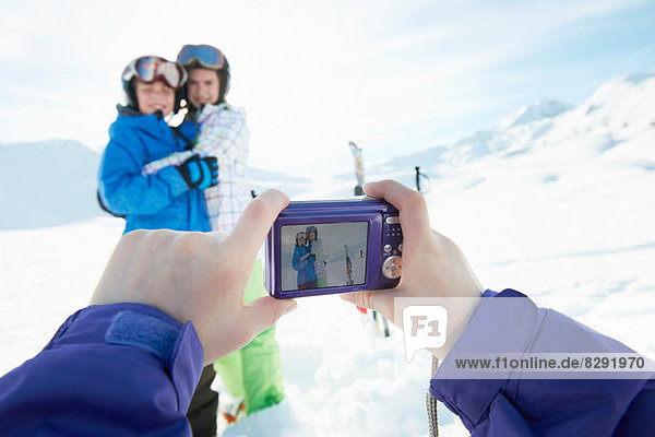 Sister photographing siblings in snow  Les Arcs  Haute-Savoie  France