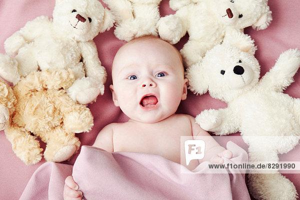 Baby Girl liegend umgeben von Plüschtieren