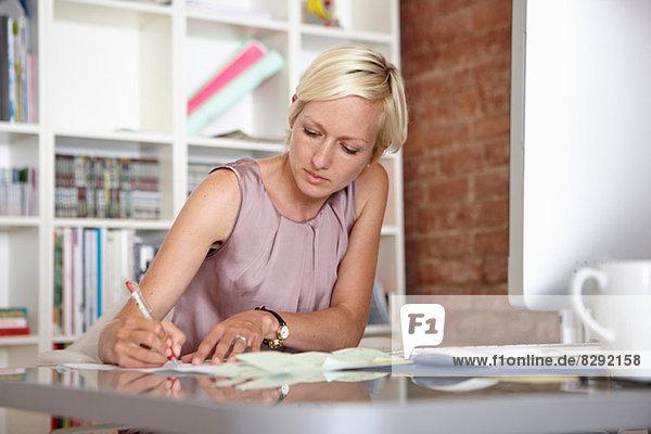 Mittlere erwachsene Frau beim Notieren am Schreibtisch
