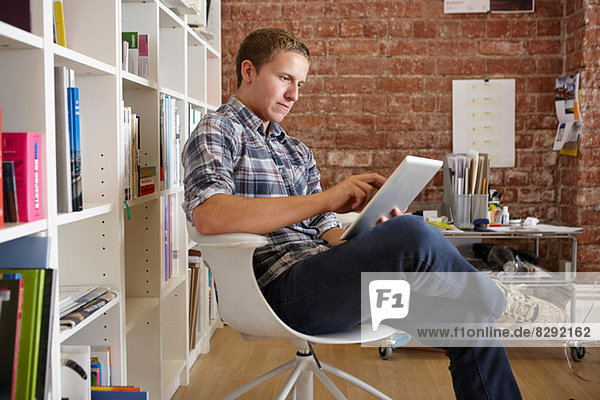 Young man sitting on chair using digital tablet