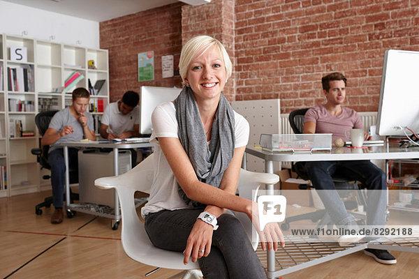 Porträt einer erwachsenen Frau auf einem Stuhl im Kreativbüro