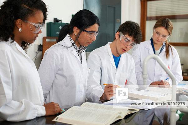 Chemielehrer und Schüler mit Lehrbüchern