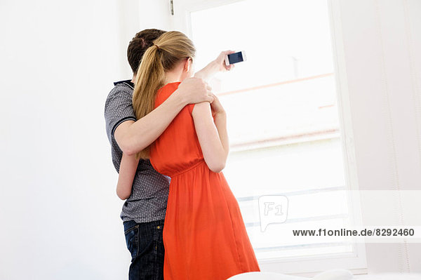 Young couple taking photograph from window