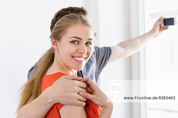 Nahaufnahme des jungen Paares beim Fotografieren aus dem Fenster