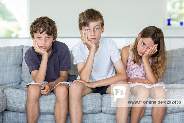 Geschwister auf dem Sofa sehen gelangweilt aus.