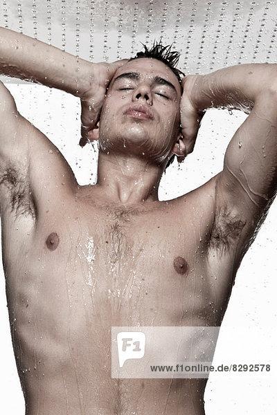 Junger Mann beim Duschen  Studioaufnahme