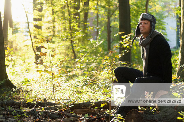 Portrait of mid adult man sitting on log in forest