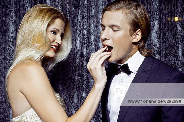 Junge Frau schenkt ihrem Freund Schokolade