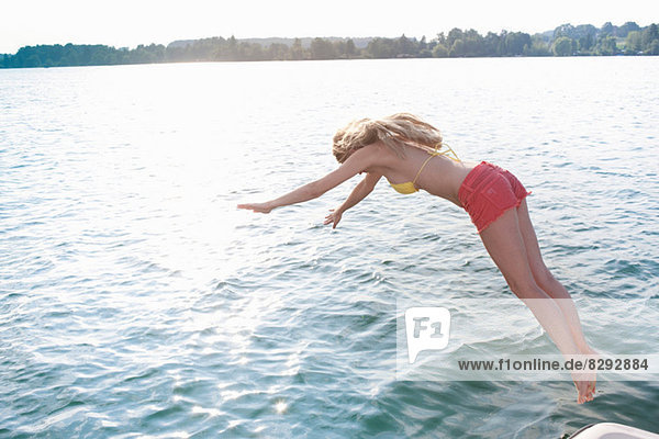 Junge Frau taucht in den See