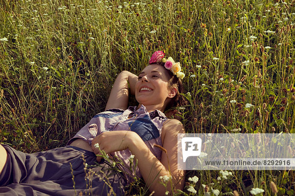 Young woman lying in meadow with flowers in her hair